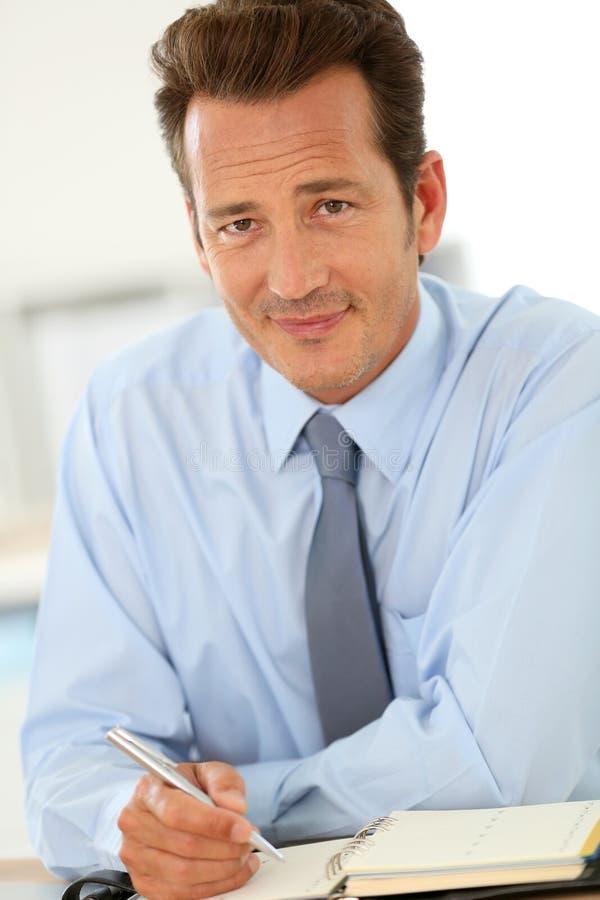 Affärsman på kontorshandstil i dagordning royaltyfri bild