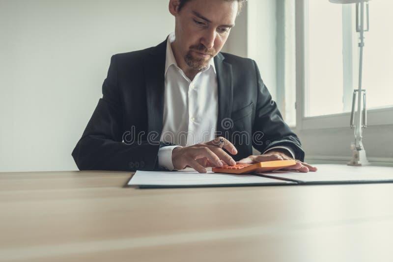 Affärsman på kontorsskrivbordet genom att använda räknemaskinen royaltyfria foton