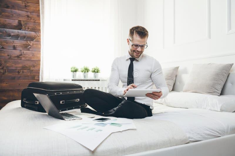 Affärsman på säng som arbetar med en minnestavla och en bärbar dator från hans hotellrum royaltyfri bild