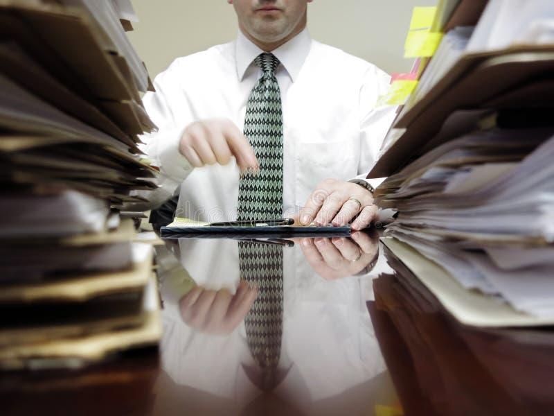Affärsman på skrivbordet med högar av mappar fotografering för bildbyråer