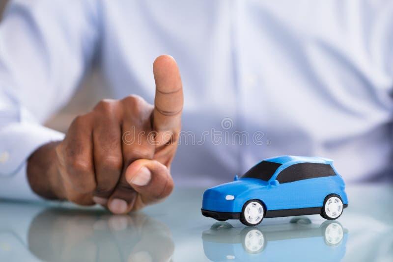 Aff?rsman Pointing Finger With Toy Car On The Desk royaltyfri foto