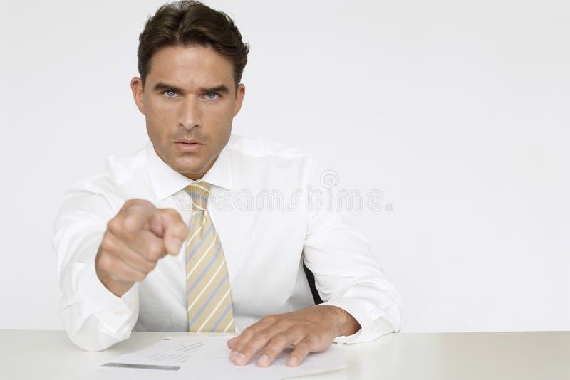 Affärsman Pointing While Sitting på skrivbordet arkivbilder