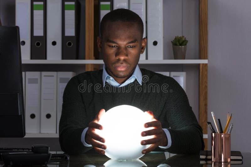 Affärsman Predicting Future With Crystal Ball royaltyfria bilder