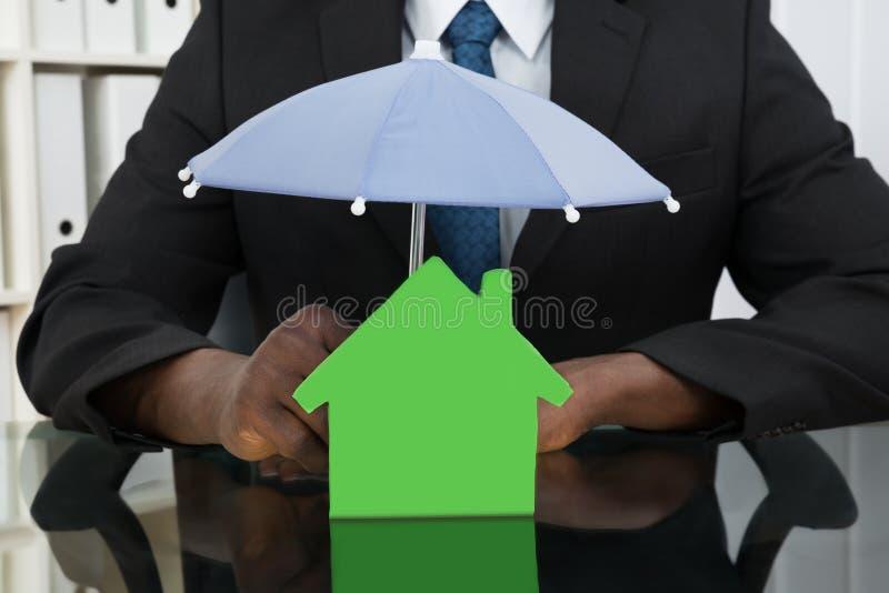 Affärsman Protecting House Model med paraplyet royaltyfri foto