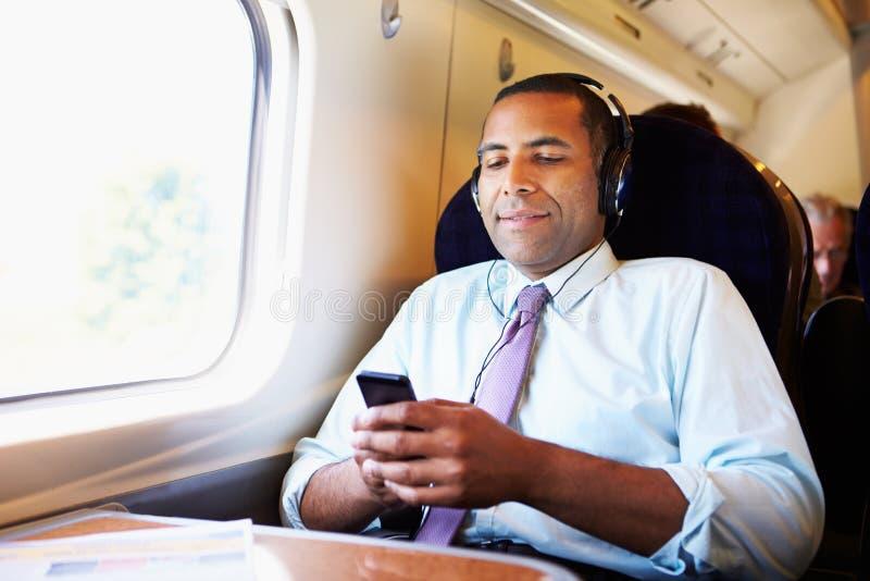 Affärsman Relaxing On Train som lyssnar till musik royaltyfri bild