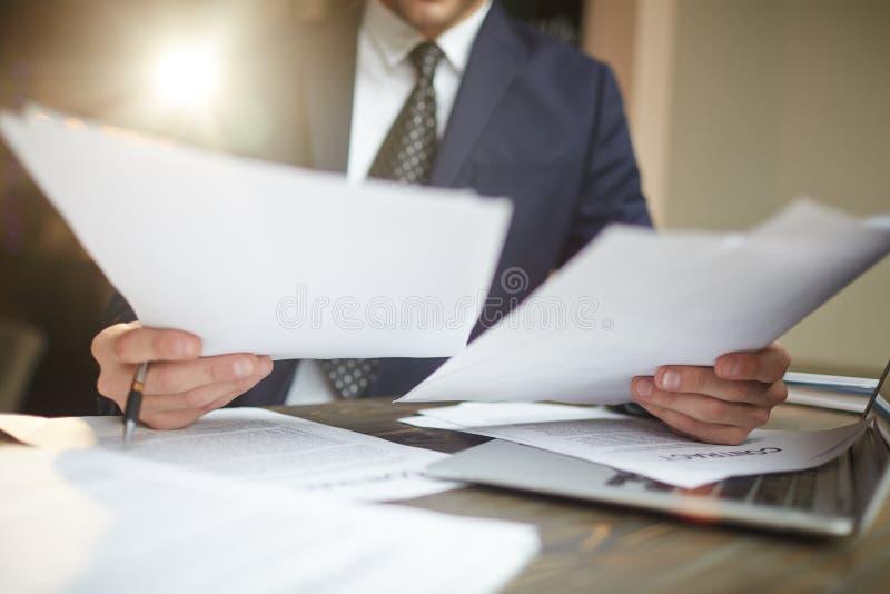 Affärsman Reviewing Paperwork för avtal arkivbild