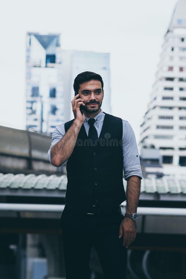 Affärsman ringer någon med mobiltelefon arkivfoto