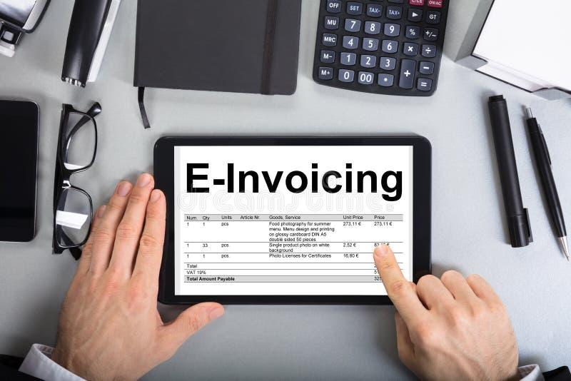 Affärsman` s räcker att gå till och med E-fakturering på den Digital minnestavlan royaltyfri bild