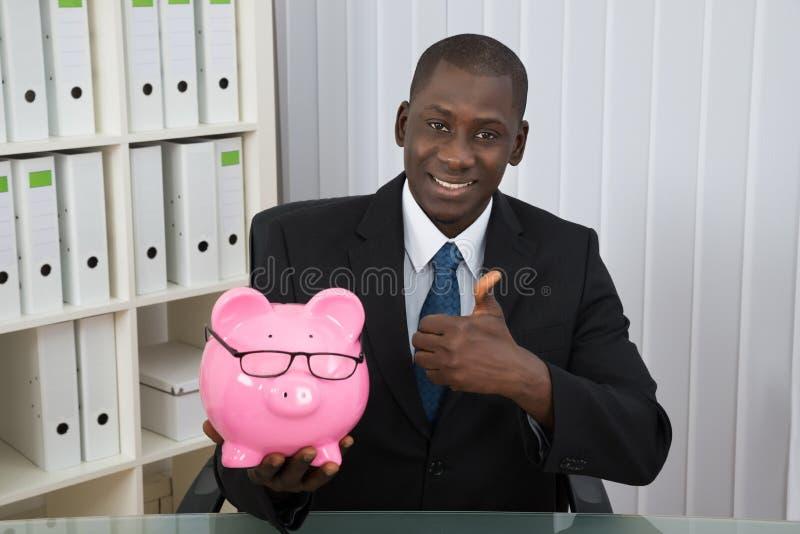 Affärsman Showing Thumb Up med Piggybank arkivbilder