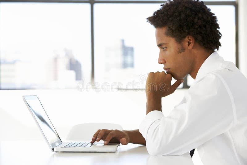 Affärsman Sitting At Desk i regeringsställning som använder bärbara datorn royaltyfria foton