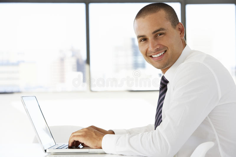 Affärsman Sitting At Desk i regeringsställning som använder bärbara datorn arkivfoto