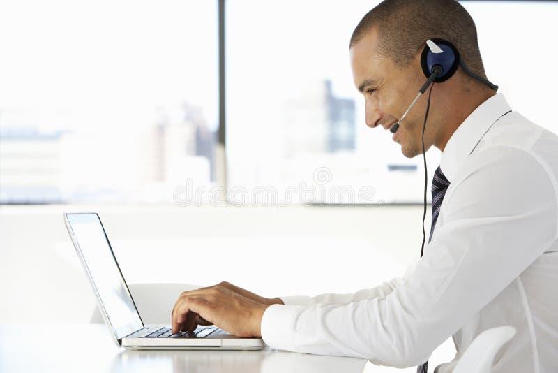 Affärsman Sitting At Desk i regeringsställning som använder den bärande hörlurar med mikrofon för bärbar dator arkivfoton