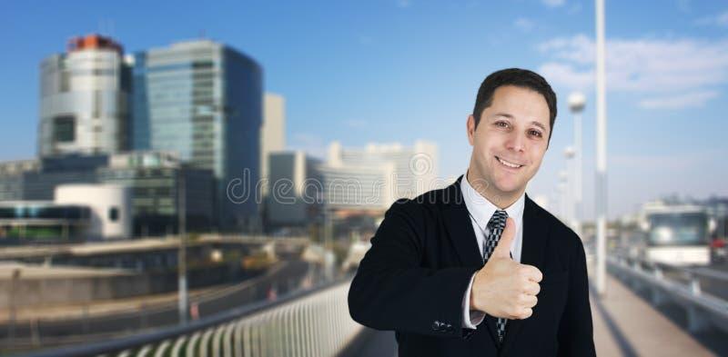 Affärsman Smiling och kännande lyckliga geende tummar upp med affärsstaden och företags byggnader i bakgrund royaltyfria foton
