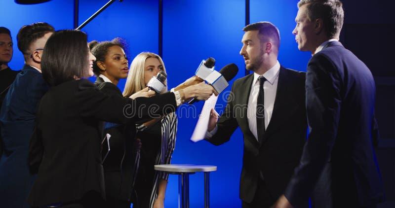 Affärsman som är bitande av intervju med reporter royaltyfri bild