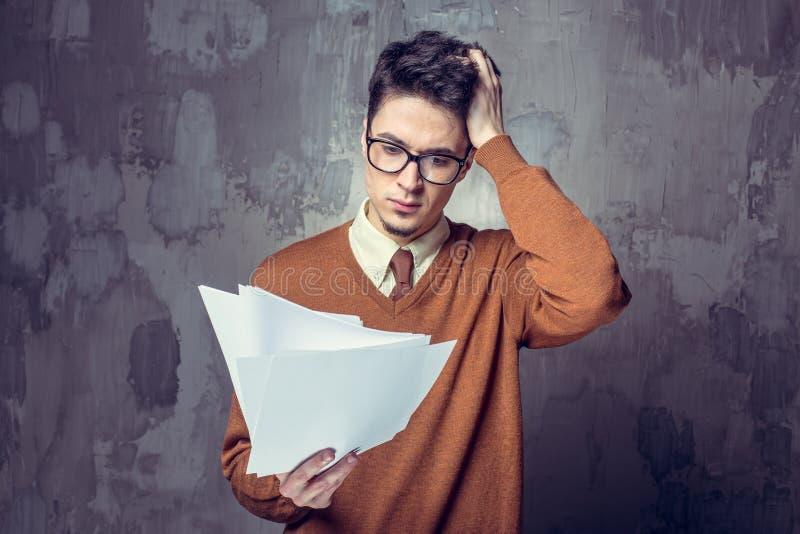 Affärsman som är förvirrad med mycket skrivbordsarbete arkivfoton
