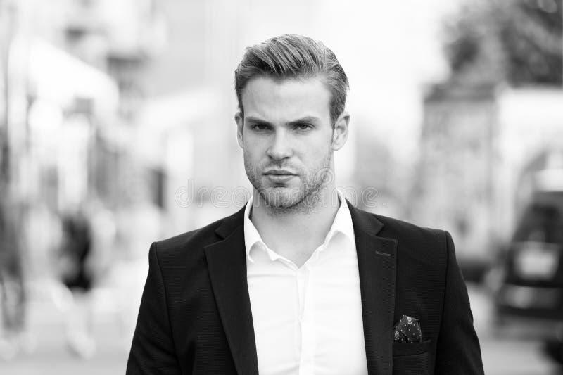 Affärsman som är klar att lösa pronlems Ansade eleganta formella dräkten för mannen går brunnen stads- bakgrund allvarlig affärsm royaltyfri bild
