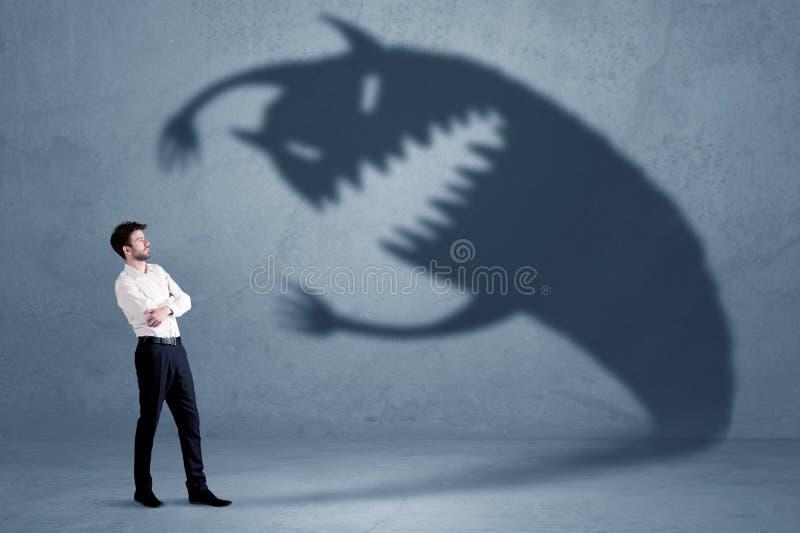 Affärsman som är rädd av hans egna skuggamonsterbegrepp royaltyfri bild