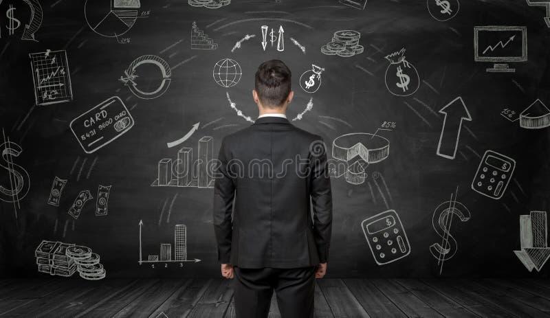 Affärsman som är stående tillbaka till oss som ser svart tavla med finansiella teckningar för krita royaltyfri illustrationer