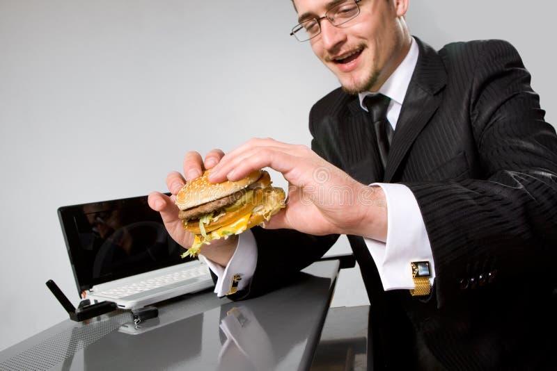 affärsman som äter den hungriga hamburgaren arkivbilder