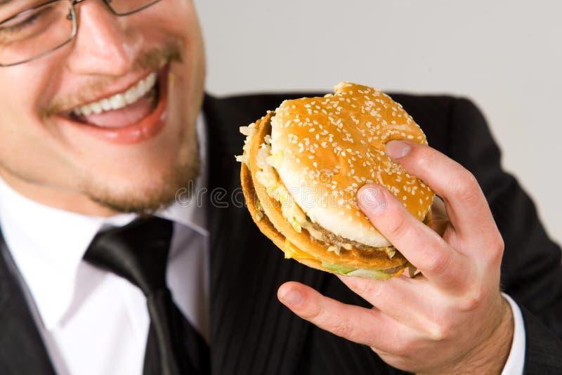 affärsman som äter den hungriga hamburgaren royaltyfria foton