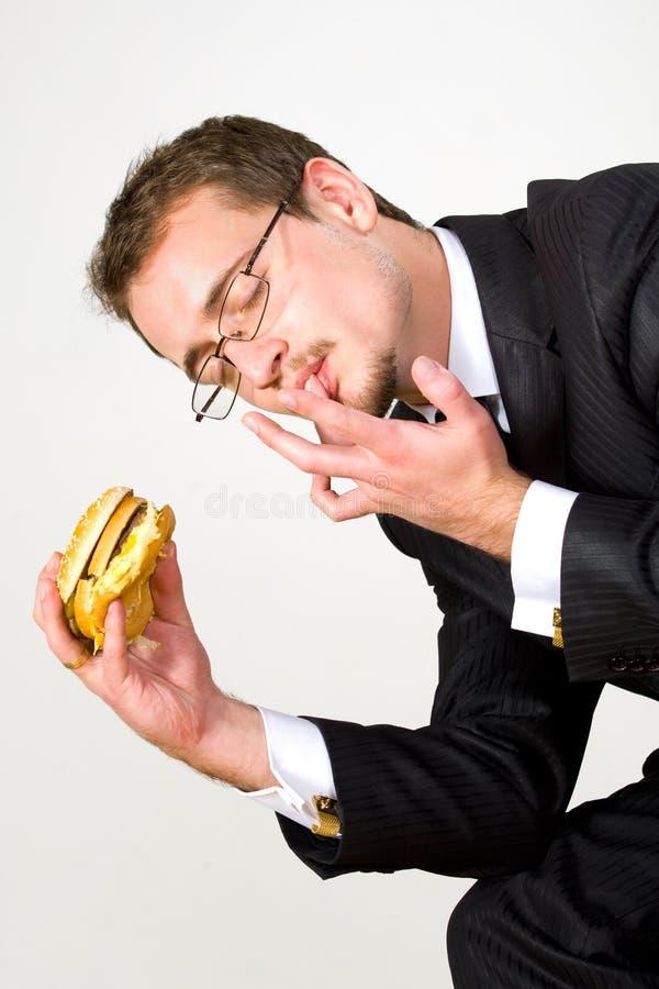 affärsman som äter den hungriga hamburgaren fotografering för bildbyråer