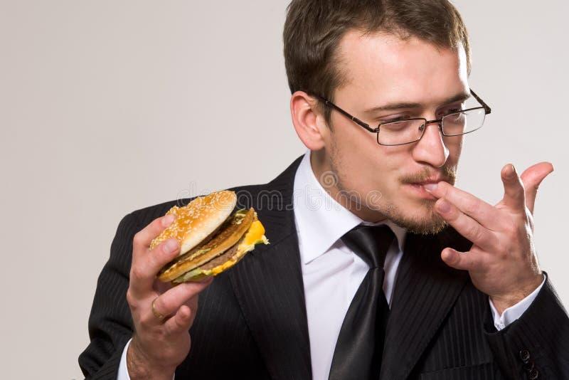 affärsman som äter den hungriga hamburgaren arkivfoto