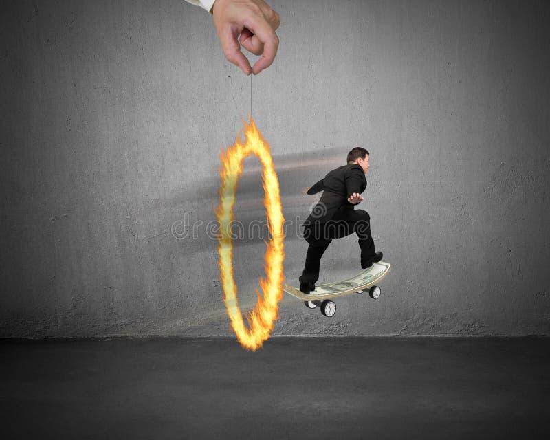 Affärsman som åker skridskor på pengarskateboarden till och med brandcirkel royaltyfri foto