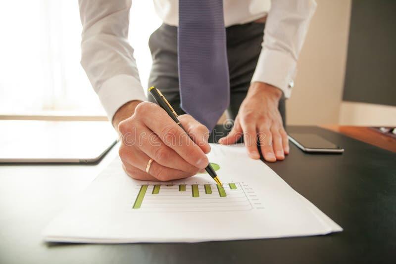 Affärsman som analyserar investeringdiagram Händer av den finansiella chefen som tar anmärkningar, när arbeta arkivbilder