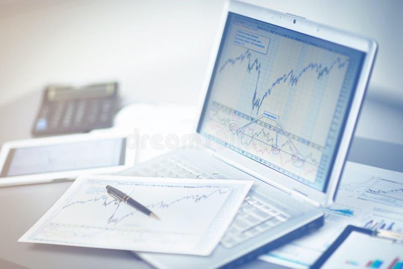 Affärsman som analyserar investeringdiagram med bärbara datorn arkivfoto
