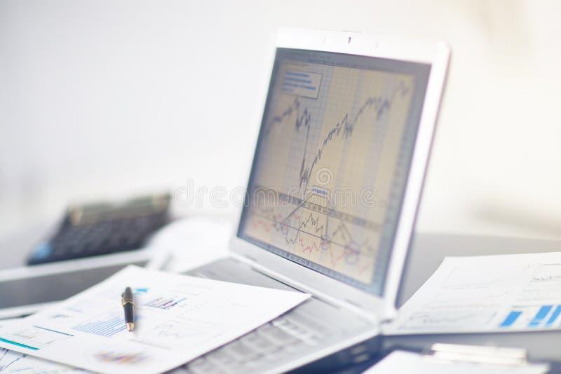 Affärsman som analyserar investeringdiagram med bärbara datorn royaltyfri bild