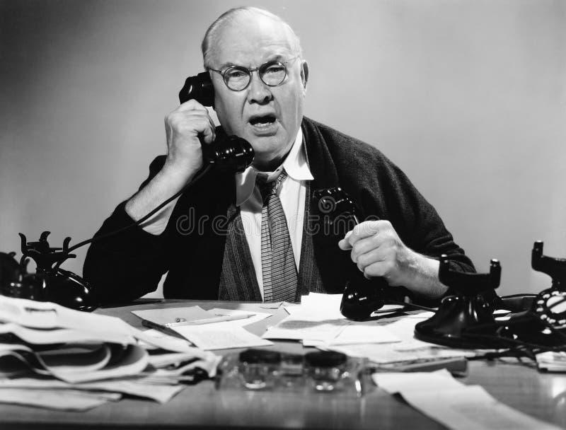 Affärsman som använder åtskilliga telefoner (alla visade personer inte är längre uppehälle, och inget gods finns Leverantörgarant royaltyfri bild