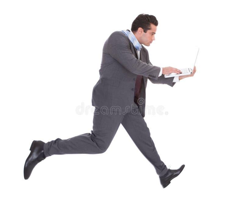 Affärsman som använder bärbara datorn, medan köra royaltyfria foton