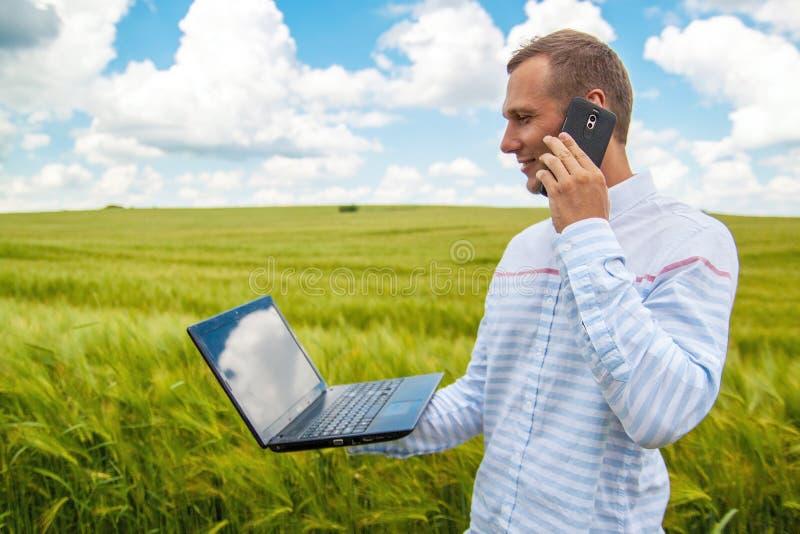 Affärsman som använder bärbara datorn och smartphonen i vetefält royaltyfri foto