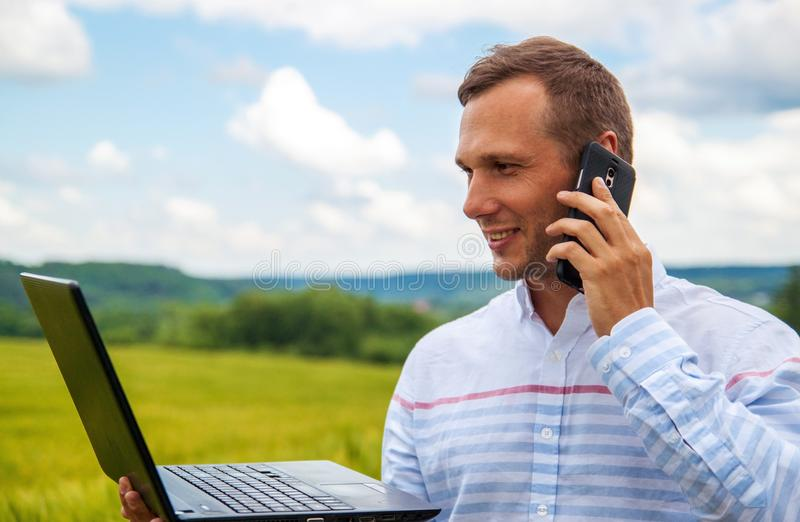 Affärsman som använder bärbara datorn och smartphonen i vetefält arkivbilder