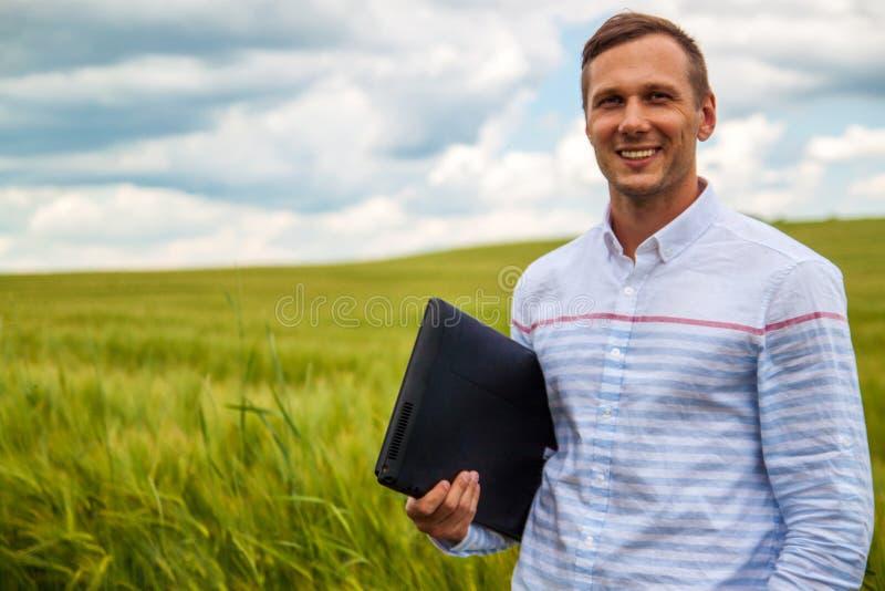 Affärsman som använder bärbara datorn och smartphonen i vetefält arkivbild