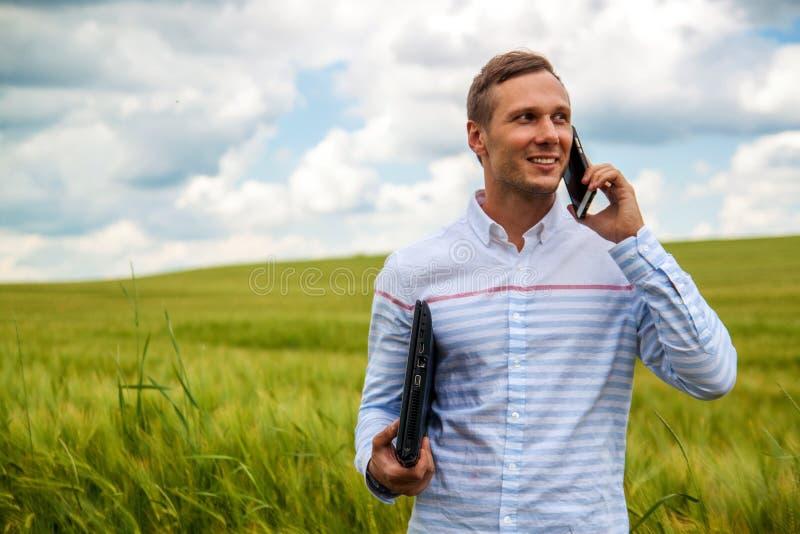 Affärsman som använder bärbara datorn och smartphonen i vetefält royaltyfri fotografi