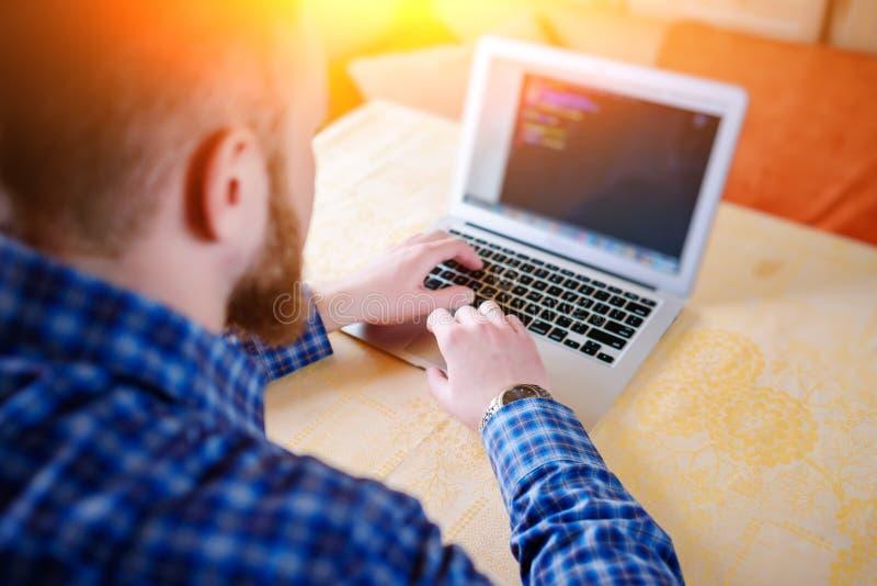 Affärsman som använder bärbara datorn på arbetsplatsen - bakre sikt arkivfoton