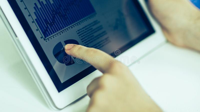 Affärsman som använder den digitala minnestavlan som arbetar med den finansiella scen royaltyfri foto