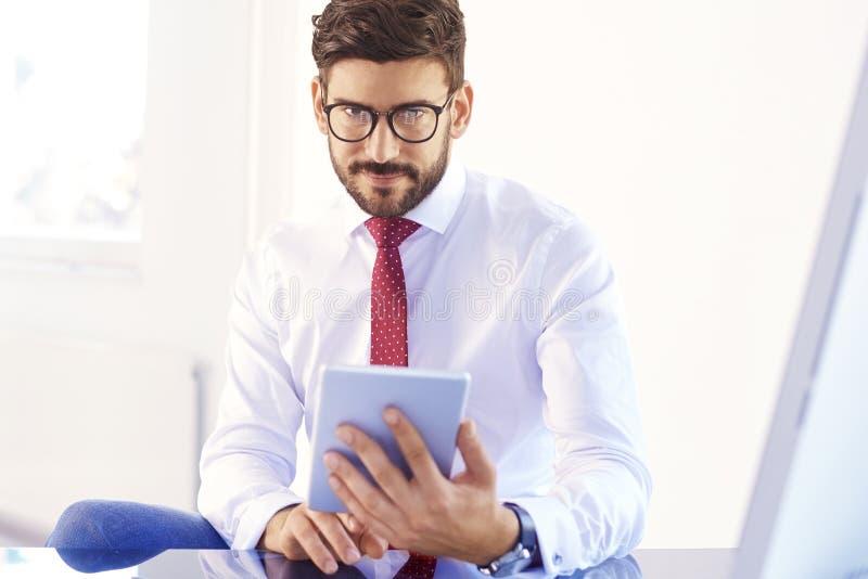 Affärsman som använder den digitala minnestavlan, medan arbeta på kontorsskrivbordet arkivfoton