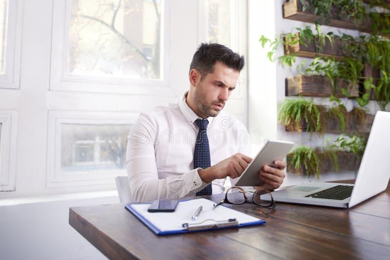 Affärsman som använder den digitala minnestavlan och datoren, medan sitta på skrivbordet och arbeta i kontoret fotografering för bildbyråer