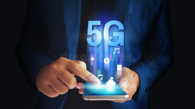 Affärsman som använder den mobila smartphonen med flöde för symboler 5G på begrepp för faktisk skärm royaltyfri bild