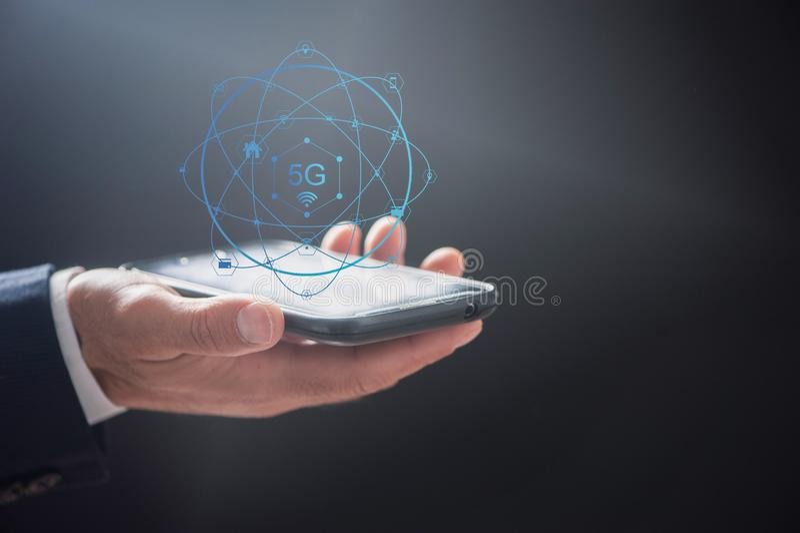 Aff?rsman som anv?nder den mobila smartphonen med fl?de f?r symboler 5G p? den faktiska sk?rmen royaltyfria bilder