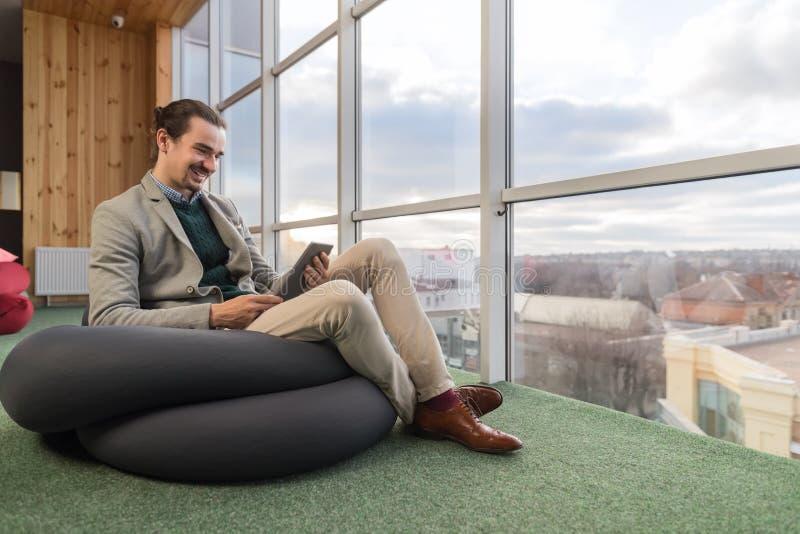 Affärsman som använder den Sit In Front Panoramic Window för cellSmart telefon affärsmannen Coworking Center arkivbild