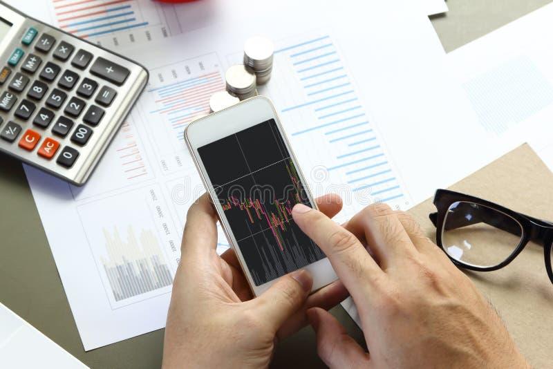 Affärsman som använder den smarta telefonen för mobil med affärsgrafen royaltyfri bild
