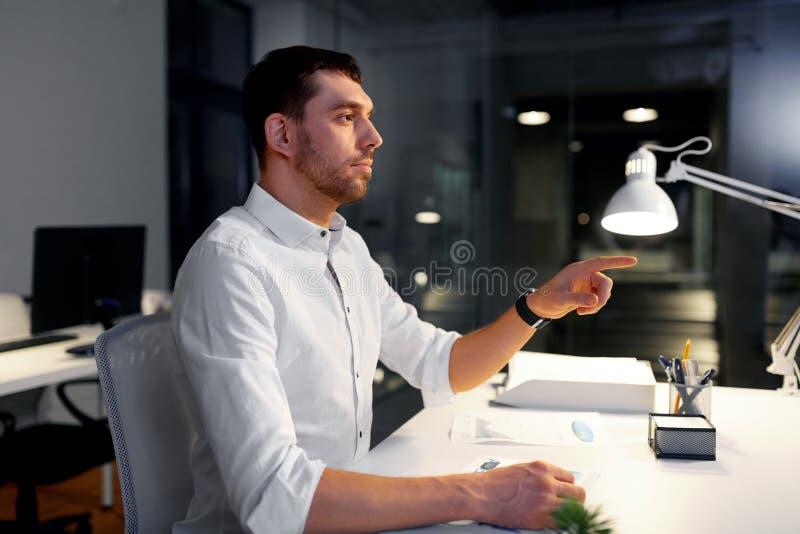 Affärsman som använder gester på nattkontoret royaltyfri foto