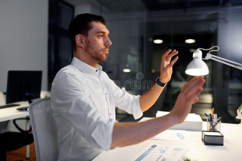 Affärsman som använder gester på nattkontoret royaltyfria foton