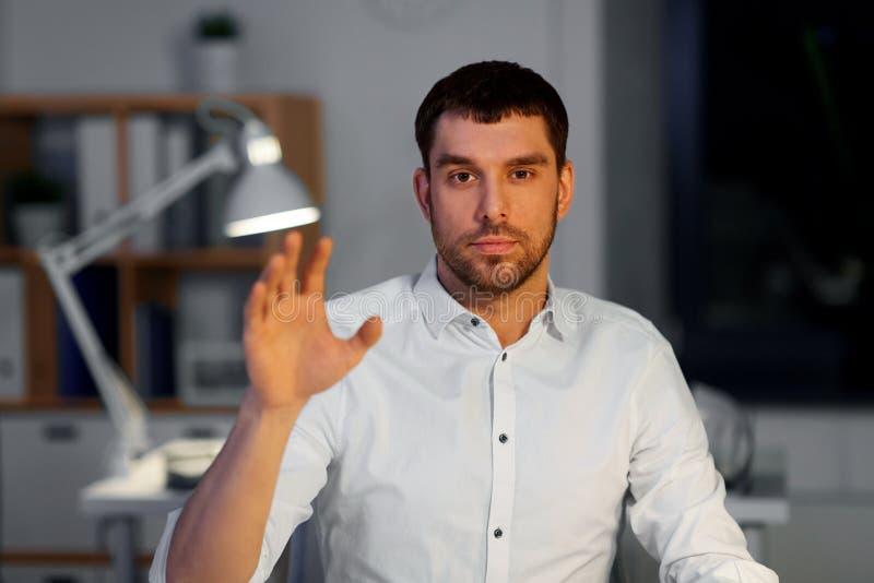 Affärsman som använder gester på nattkontoret royaltyfri fotografi
