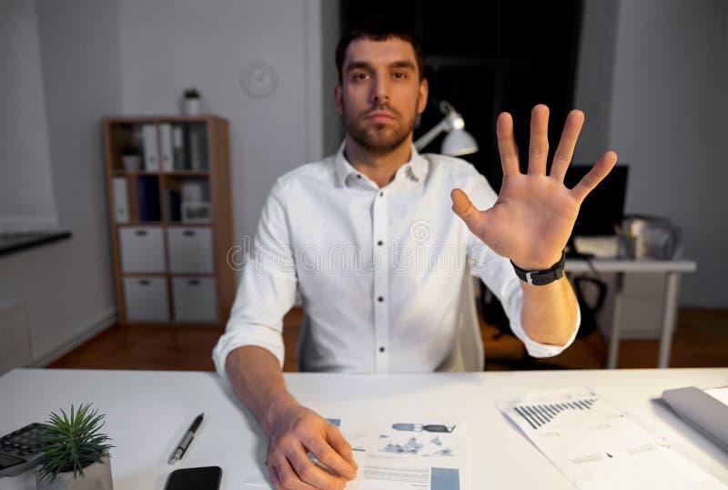 Affärsman som använder gester på nattkontoret arkivfoto