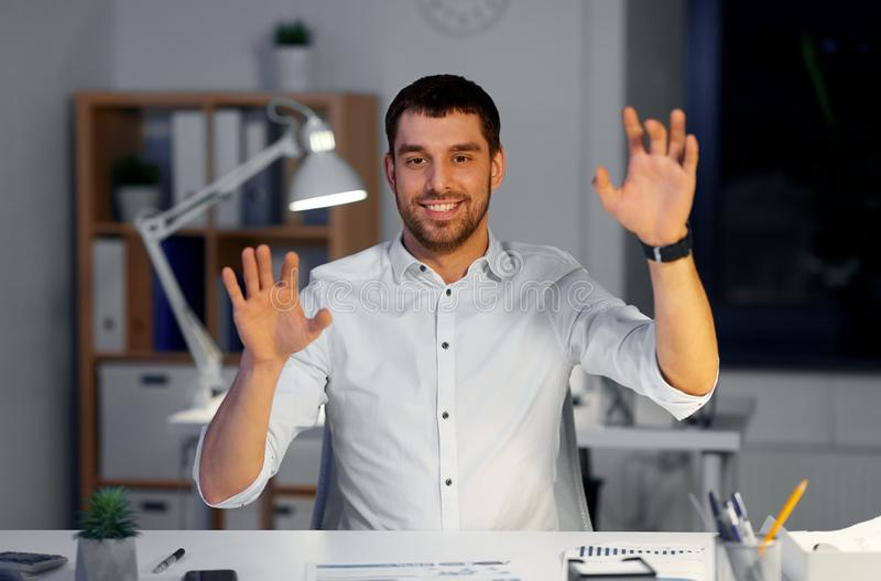 Affärsman som använder gester på nattkontoret fotografering för bildbyråer