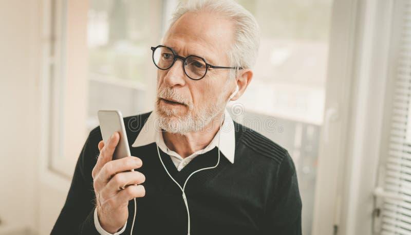 Affärsman som använder hörlurar under konversation på mobiltelefonen royaltyfri fotografi